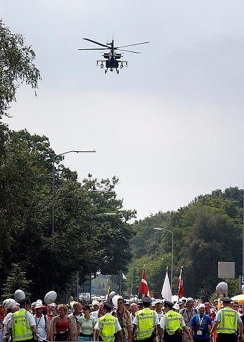 Nederland, Nijmegen, 23-7-2004<br /> Terwijl politie de wandelaars afremt voor een verkeerskruising vliegt een Appache helikopter over de St Annastraat als groet aan de militairen van vliegbasis Volkel<br /> Intocht vierdaagse, 4daagse, veiligheid evenement, terreurdreiging, politieinzet, soft target.<br /> Foto: Flip Franssen/Hollandse Hoogte