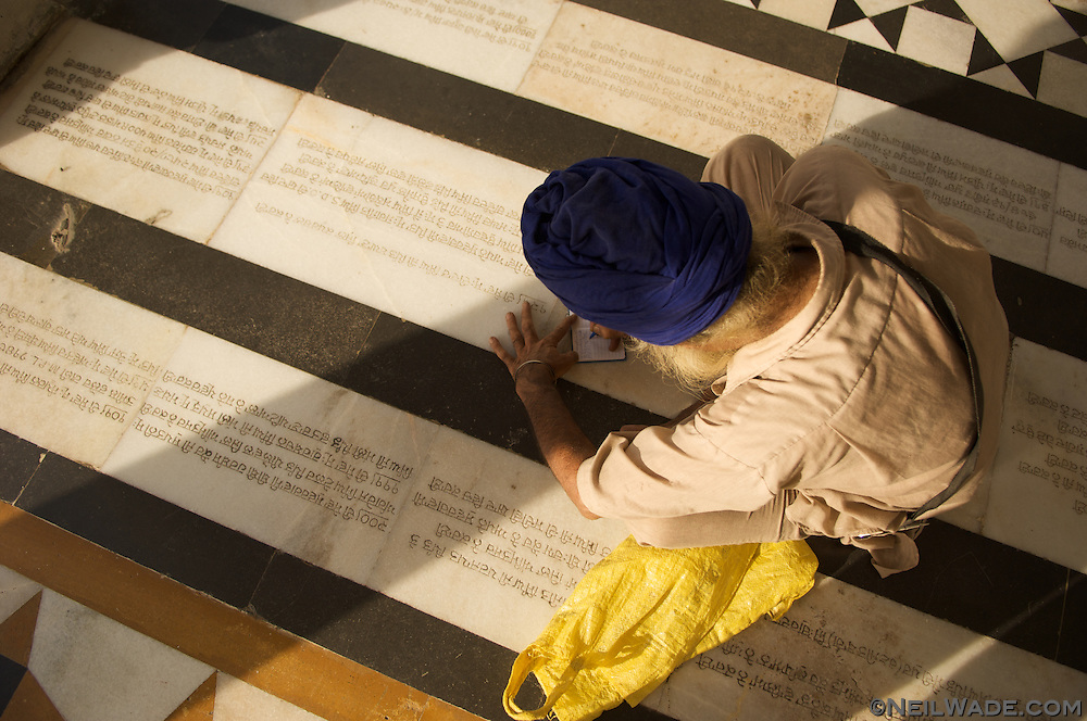 A Sikh man writes his address so that I can send him a prit of his portrait (not shown).  On the floor are Sikh prayers.