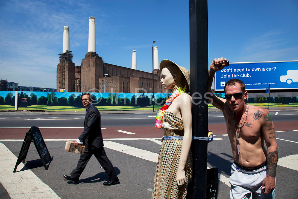 Street scene with a tattooed man, a manequin and a businessman by Battersea Power Station in South London. This classic Art Deco brick design with it's distinctive four white towers is one of London's most famous landmarks. Now derelict and with plans for possible development, it remains one of the iconic designs which towers over the River Thames.