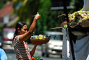 Woman sprinkling holy water on offering. Sanur, Bali, Indonesia