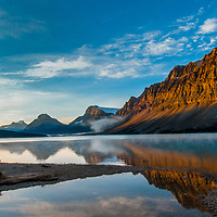 A photographer shoots mist rising over Bow Lake as dawn breaks on Mount Andromache, Mount Hector, Bow Peak, Bow Crow Peak and Crowfoot Mountain in Banff National Park, Alberta, Canada.