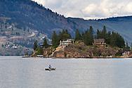A Fisherman rowing a boat on Okanagan Lake near Ellison Provincial Park in Vernon, British Columbia, Canada
