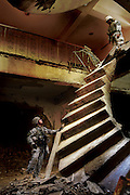 U.S. Army 2nd Lt. Jonathan Hicks attempts to access the upper levels of a building, which was just recaptured from enemy insurgents in Baqubah, Iraq on Jan. 22, 2007. The staircase hangs precariously from the second story after being heavily bombed by American fighter jets during the battle to recover the key location. Hicks' translator managed to climb the obstacle to be sure the entire building was free of enemy forces.