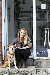 March 16, 2018 - Smiling female owner of plant shop sitting on steps outside her store, a dog sitting next to her. (Credit Image: © Mint Images via ZUMA Wire)