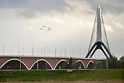 Nederland, Nijmegen, 3-11-2013De nieuwe stadsbrug van de stad Nijmegen, de Oversteek, genoemd naar de heldhaftige oversteek van de rivier de Waal die Amerikaanse soldaten op dit punt maakten tijdens de operatie Market Garden in de tweede wereldoorlog om met succes de oude Waalbrug te veroveren.De Oversteek is een boogbrug van 285 meter lang en 60 meter hoog en is de op een na langste hoofd overspanning van Nederland, en de grootste boogbrug van Europa met een enkelvoudige boog.De brug wordt 23 november in gebruik genomen.De nieuwe oeververbinding moet zorgen voor een betere spreiding en doorstroming van verkeer binnen de stad Nijmegen. Na 75 jaar is er eindelijk een tweede vaste verbinding voor de stad. De oude waalbrug krijgt vanaf eind dit jaar groot onderhoud, waarna de volle capaciteit van beide bruggen pas gebruikt kan worden. De skyline van de stad is voorgoed veranderd.Foto: Flip Franssen/Hollandse Hoogte
