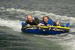 United States, Washington, Bellevue, father and daughter (age 8) tubing behind boat on Lake Washington