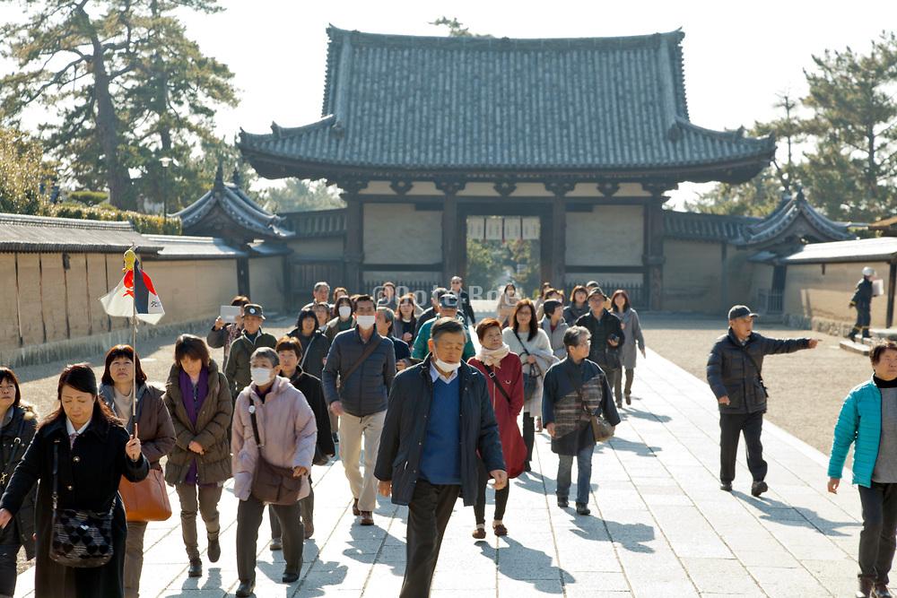 mass tourism entering the Horyuji temple grounds Nara prefectrure Japan