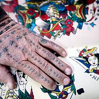 Nederland, Amsterdam , 27 oktober 2011..De linkerhand van tattoo meester Henk Schiffmacher op eenTattoo tekening uit het  Tattoo Museum op de Plantage Middenlaan nr 62..Amsterdam Tattoo Museum and the most famous Dutch tattoo-artist Henk Schiffmacher with his historical materials.