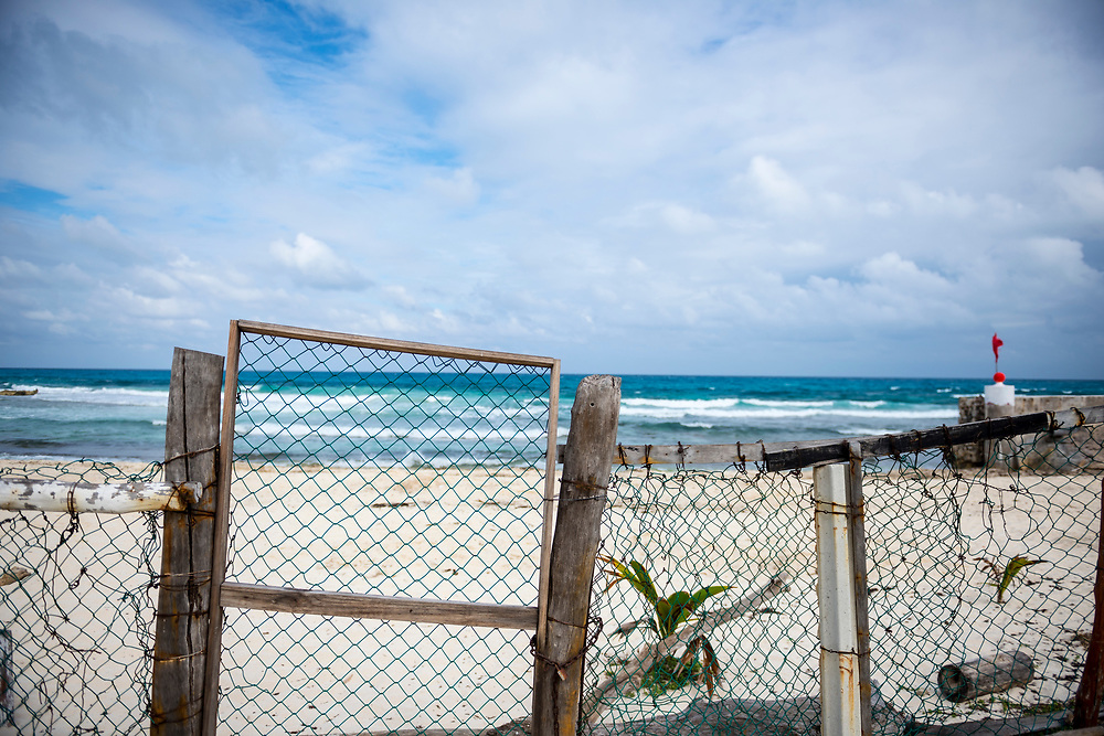 Old chain link fence and locked gate at the beach. Location is Isla Mujeres, Mexico