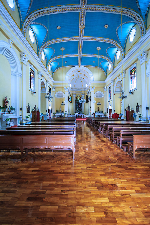 St. Lawrence Church in Macau, China. The church has a rich interior with wooden ceiling in turquoise, white and gold beams, intricate woodwork and hanging chandeliers.