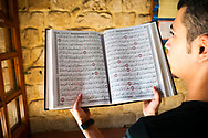 Sidon, Lebanon - September 24, 2010: A young man holds the Qur'an inside the 13th-century Bab al-Saray Mosque in Sidon, Lebanon.