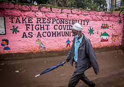 May 2, 2020, Nairobi, Kenya: A man wearing a face mask as a precaution, walks past a wall with an awareness graffiti during the corona virus pandemic..Daily life in Kibera slums the largest in Nairobi, has not been greatly affected by the ongoing covid19 pandemic except for a few activities limited by the imposed curfew due to the pandemic. (Credit Image: © Donwilson Odhiambo/SOPA Images via ZUMA Wire)