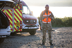 "© Licensed to London News Pictures . 28/06/2018 . Saddleworth , UK . Wing Commander GARY LANE Lane (l), RAF Regional Liaison Officer for the North West at Higher Swineshaw Reservoir . The army are being called in to support fire-fighters , who continue to work to contain large wildfires spreading across Saddleworth Moor and affecting people across Manchester and surrounding towns . Very high temperatures , winds and dry peat are hampering efforts to contain the fire , described as "" unprecedented "" by police and reported to be the largest in living memory . Photo credit: Joel Goodman/LNP"