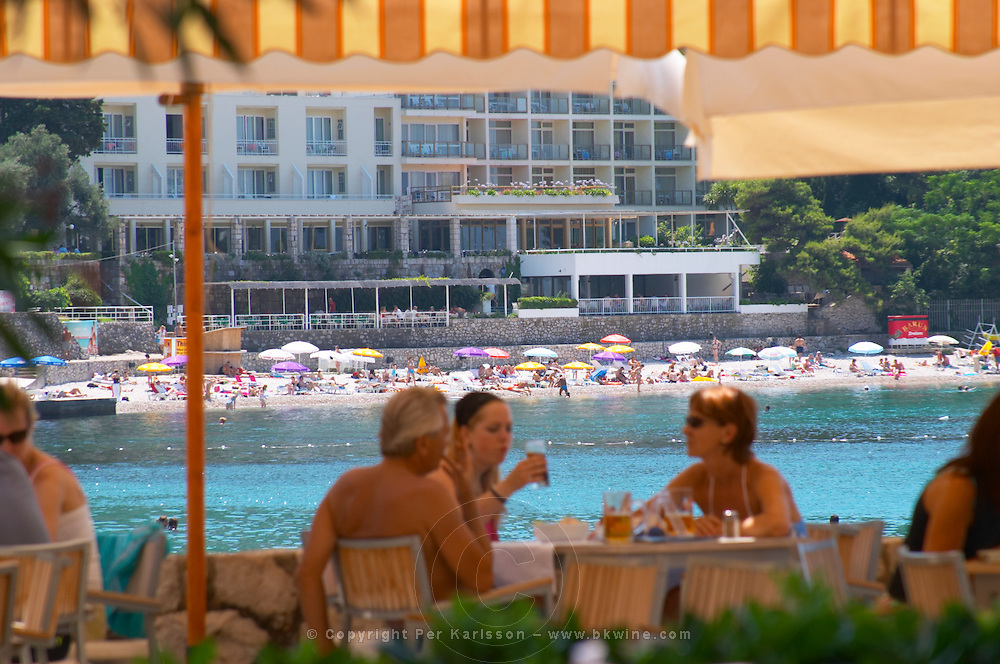 In the foreground, fuzzy: Seaside Restaurant outside seating terrace. Guests sitting eating and drinking in the shade. In the background: hotels, beach and sea. Hotel and restaurant Kompas. Uvala Sumartin bay between Babin Kuk and Lapad peninsulas. Dubrovnik, new city. Dalmatian Coast, Croatia, Europe.