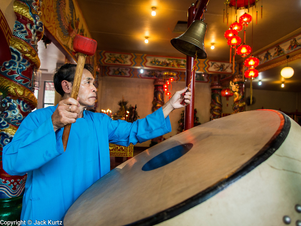 "09 FEBRUARY 2014 - HAT YAI, SONGKHLA, THAILAND: A man beats a prayer drum in the Chao Mae Tubtim Shrine (Ruby Goddess Shrine) on 108 Hainanese Ancestors Memorial Day in Hat Yai, Songkhla, Thailand. Hainanese communities around the world celebrate ""108 Hainanese Ancestors Memorial Day."" The day honors the time when 109 Hainanese villagers fleeing life in Hainan (an island off of the southwest coast of China, near Vietnam) washed up in what is now Vietnam and were killed by Vietnamese authorities because authorities thought they were pirates. The Vietnamese built a temple on the site and named it ""Zhao Yin Ying Lie."" Many Vietnamese fisherman credit prayers at the temple to saving their lives during violent storms and now ""108 Hainanese Ancestors Memorial Day"" is celebrated in Hainanese communities around the world. Hat Yai, the economic center of southern Thailand has a large Hainanese population.    PHOTO BY JACK KURTZ"