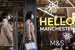 © Licensed to London News Pictures. 31/10/2020. Manchester, UK. Two women walk past a Manchester window display. The wet weather and tier 3 restrictions don't deter some people in Manchester today. Photo credit: Kerry Elsworth/LNP