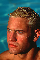 Headshot of a blue eyed blond man in a swimming pool