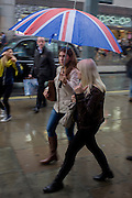 Londoners walk along central London's Oxford Street during autumnal rain.