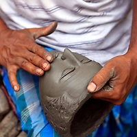 Asia, India, Calcutta. Sculptor hands work on face the potter's village of Kumartuli in Calcutta.