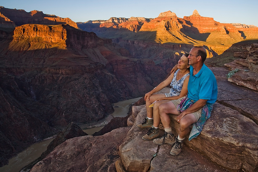An adult couple sit together looking down at the Colorado River from Plateau Point, Grand Canyon National Park, Arizona on September 20, 2006. The viewpoint is a short hike from Indian Garden campground on the Bright Angel Trail.