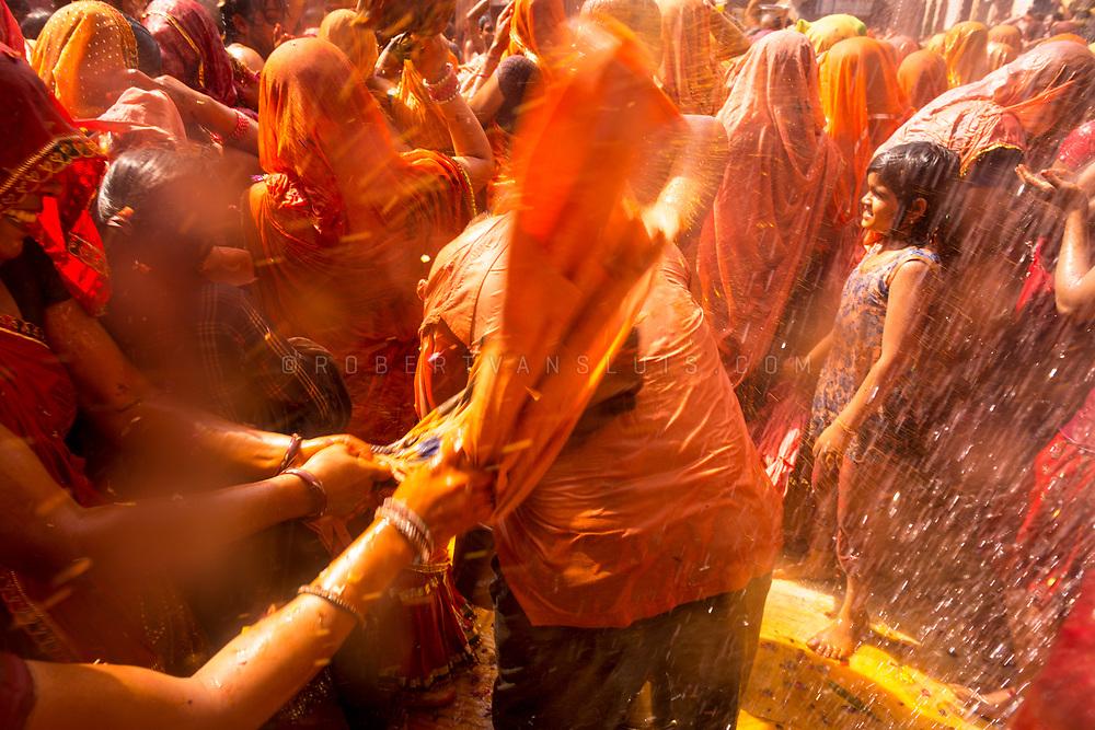Women hit a man with wet clothes at the Huranga festival, Dauji temple, Baldeo, India. Photo ©robertvansluis.com