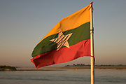 The flag of Myanmar blowing in the wind at sunset on the bow of a boat on the Irrawaddy River