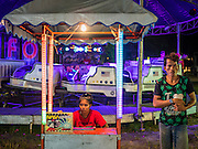 """15 JUNE 2105 - NARATHIWAT, NARATHIWAT, THAILAND:  """"Carneys"""" wait for people to ride their attraction at a fair in Narathiwat to celebrate 100 years of Narathiwat. The city has been a Muslim city for centuries, but when Siam (now Thailand) annexed the three southern provinces they changed the name to Narathiwat.     PHOTO BY JACK KURTZ"""