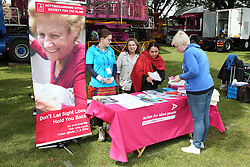 Out reach workers from a charity for blind people at festival stall with information poster and leaflets.