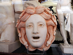 Detail of carved stone head of Medusa in window display of antique shop in Kerkyra town on Corfu Island Greece