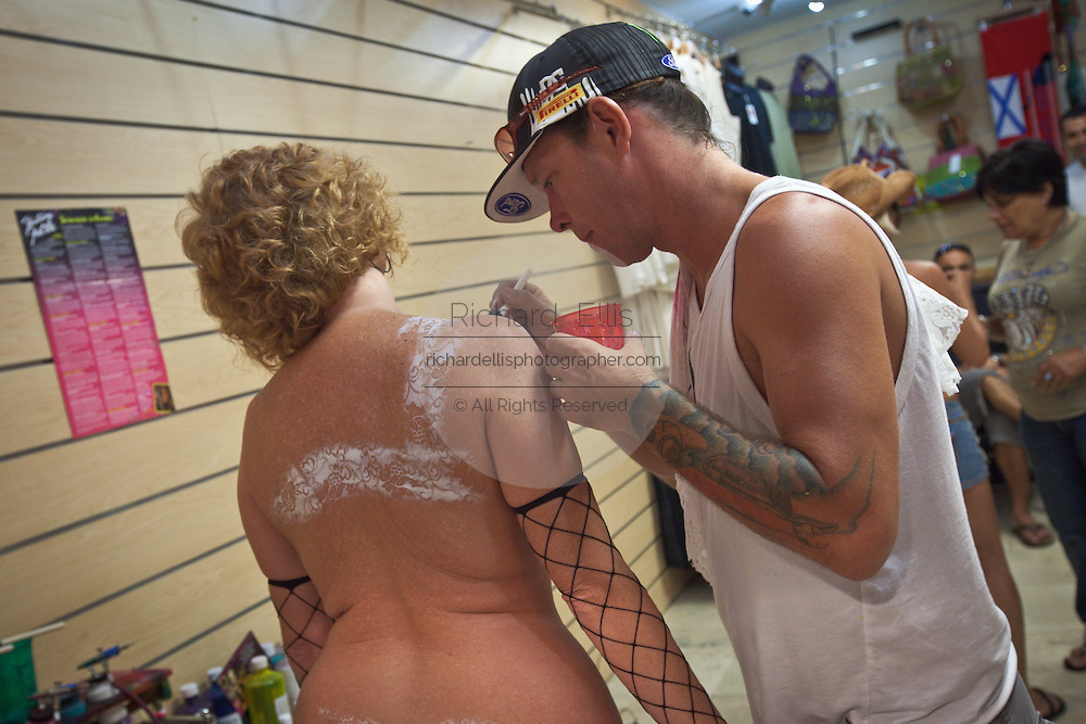 A tourist has body paint applied during Fantasy Fest halloween parade in Key West, Florida.