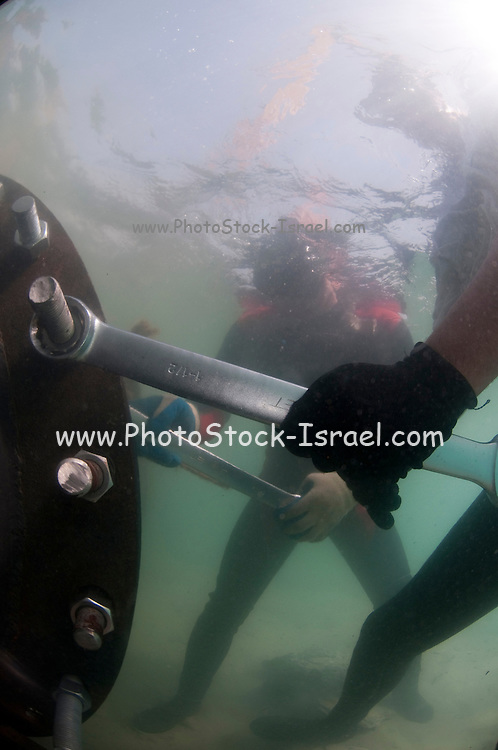 Workers laying a brine discharge pipe from a desalination plant on the seabed to a distance of 300 meter from the shore. Fastening the pipe to the brine discharge outlet. Brine discharge can have a negative impact on the ocean ecosystem. Photographed in Israel Mediterranean sea