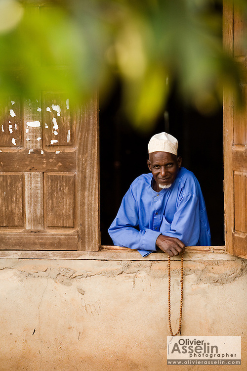 An elderly man stands in the window of a mosque in the village of Boulembe, near Bertoua, Cameroon, on Tuesday September 15, 2009.