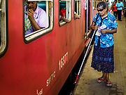 07 OCTOBER 2017 - COLOMBO, SRI LANKA: A blind lottery vendor walks along a train at the Fort Station in Colombo. The Fort Station is Colombo's main train station and serves as the hub of Sri Lanka's train system. The station opened in 1917 and is modeled after Manchester Victoria Station.    PHOTO BY JACK KURTZ