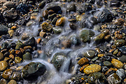 A stream of water flows over river rocks along the Snoqualmie River near Fall City, Washington.