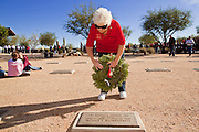 09 DECEMBER 2011 - PHOENIX, AZ:  PAMELA BELLMAN lays a Christmas wreath on a veteran's grave in Phoenix Saturday. Bellman and her husband bought 15 years wreaths this year for graves. They've been participating in the wreath laying ceremony for years. Several hundred volunteers and veterans gathered at the National Memorial Cemetery of Arizona in Phoenix Saturday to lay Christmas wreaths on headstones, a tradition started by Wreaths Across America. Wreaths Across America is a nonprofit organization founded to continue and expand the annual wreath laying ceremony at Arlington National Cemetery begun by Maine businessman, Morrill Worcester, in 1992.   PHOTO BY JACK KURTZ