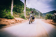 A couple rides a minsk motorbike off the beaten track in Ha Giang Province, Vietnam, Southeast Asia