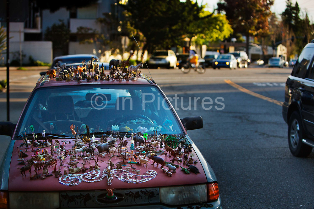 Parked car on Claremont Avenue, Berkeley, California, decorated with assorted animal and toy figures