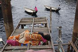April 28, 2018 - Dhaka, Bangladesh - A homeless boy sleeps on a bridge as boatmen run for passenger for in the Shore of Buriganga River. (Credit Image: © Md. Mehedi Hasan via ZUMA Wire)