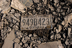 30 Sept, 2005.  New Orleans, Louisiana. Lower 9th ward.  Hurricane Katrina aftermath. <br /> The remnants of the lives of ordinary folks, now covered in mud as the flood waters remain. A Louisiana licence plate lies in the drying mud.<br /> Photo; ©Charlie Varley/varleypix.com