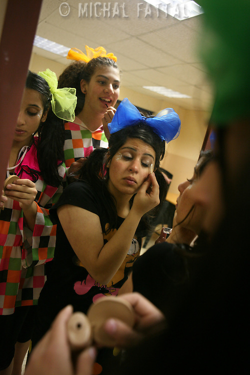"""Members of The Palestinian Circus School put on their make up before going on stage, as they prepare to perform the show """"Circus behind the wall"""" in Ramallah, November 20, 2009.The circus group was established in 2006, in order to give a new way of expression for Palestinians, and a new way to deliver the idea of resistance to the occupation. This performance is based on the life of Palestinians behind the separation wall. Photo by Michal Fattal/backyard"""