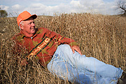 Hunter Joe Moores lays waiting for his fellow hunters to return from upland game hunting in the North Dakotan landscape near to Minot. Joe is an experienced hunter.