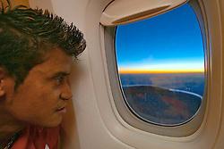 Adriano Gabiru observa a paisagem do amanhecer pela janela do boeing 474 no voô de volta ao Brasil. FOTO: Jefferson Bernardes/Preview.com
