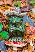 Frog figurine on an Amanita mushroom, domestic garden, autumn, November, private residence, Tacoma, Washington, USA