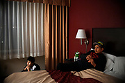 Rafael Febres and his son John in their hotel room at the Red Roof Inn, Friday, Jan. 26, 2018, in Hartford, Conn.  Febres, his wife Janette and son who are from Puerto Rico and displaced by Hurricane Maria have all been sharing one bed in a hotel room without a refrigerator since November. (Jessica Hill for the New York Times)