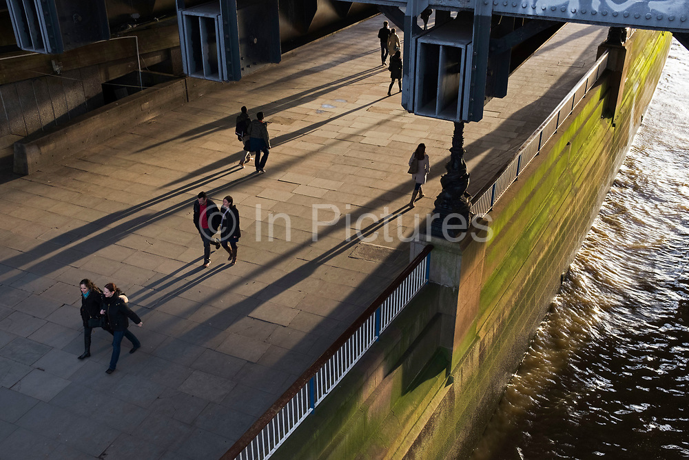 People walking along the riverside walkway underneath Hungerford Bridge on a Winter's evening in beautiful light on the Southbank, London, United Kingdom. The South Bank is a significant arts and entertainment district, and home to an endless list of activities for Londoners, visitors and tourists alike. (photo by Mike Kemp/In Pictures via Getty Images)
