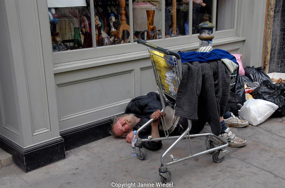 Homeless man asleep in a doorway of shop in Brick Lane East london.