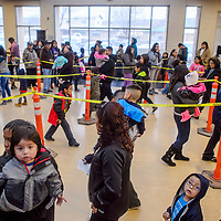 A crowd of parents and children wait in a long queue during the Toys for Tots event at the Zuni Wellness Center in Zuni Thursday.