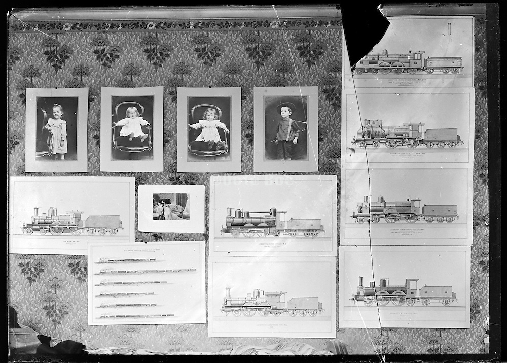 broken glass plate of wall with children portraits and architecture drawings of steam trains Paris around 1900