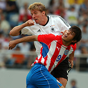 Germany's Marko Rehmer wins the ball in the air from Paraguay's  Roque Santa Cruz