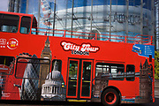 A tour bus drives beneath a large advert for American Airlines of a wide-bodied airliner in Waterloo, south London. Images of the capital's famous landmarks including The Millennium Wheel, the Gherkin, St Paul's and Tower Bridge, are seen on the side of the bus. Above is a large billboard advertising American Airlines, their wide-bodied airliner seemingly flying across the landscape.